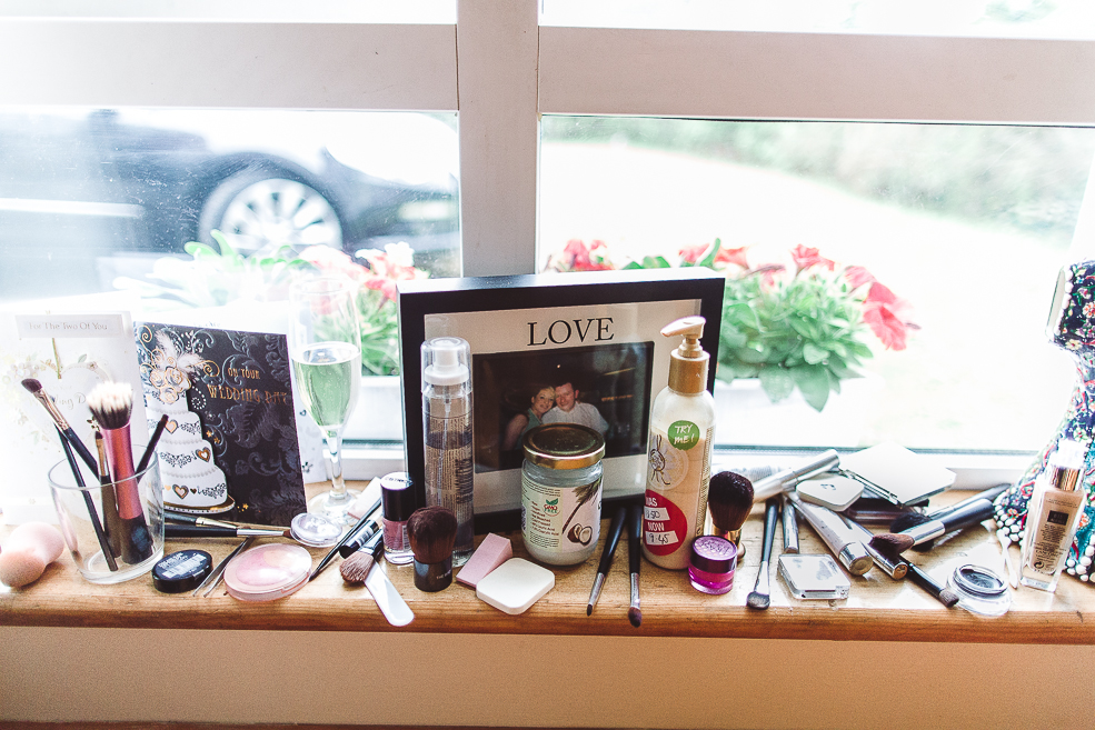 A photo and makeup accessories sitting on top of a wooden table