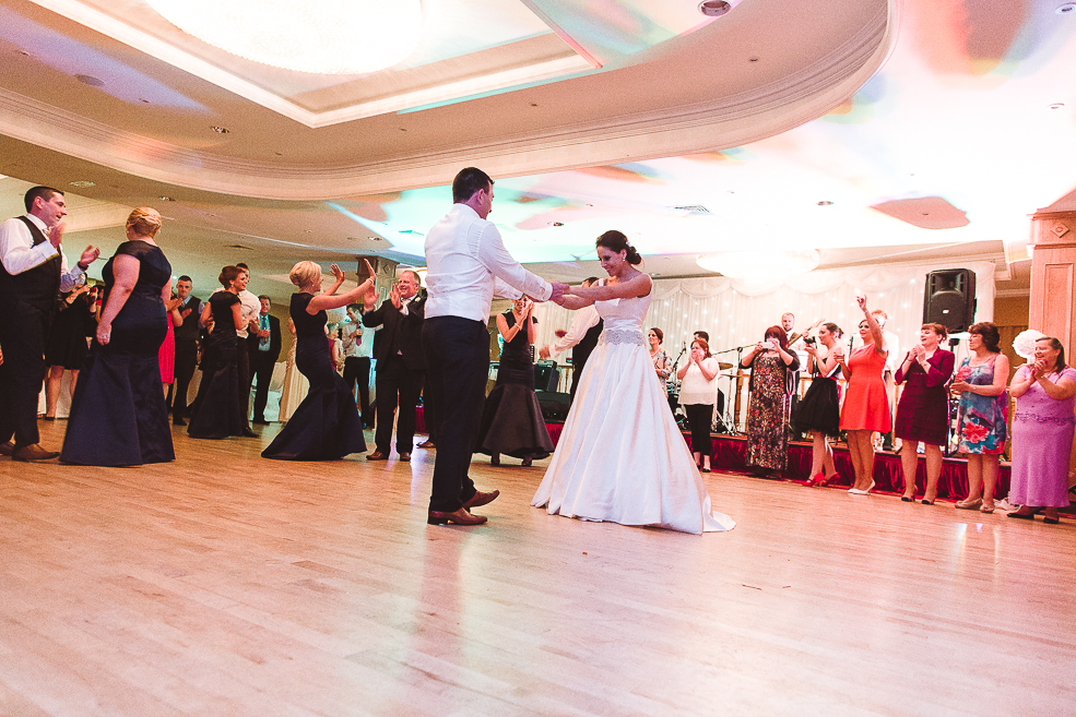 The newlyweds dancing on top of a wooden floor during the wedding party