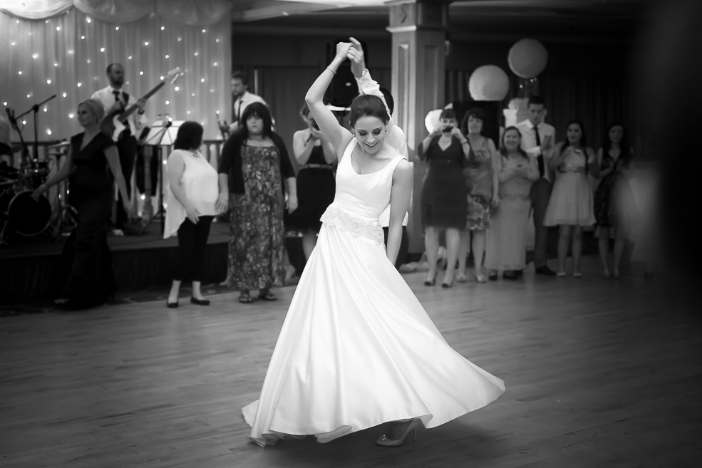 A bride in a white dress dancing