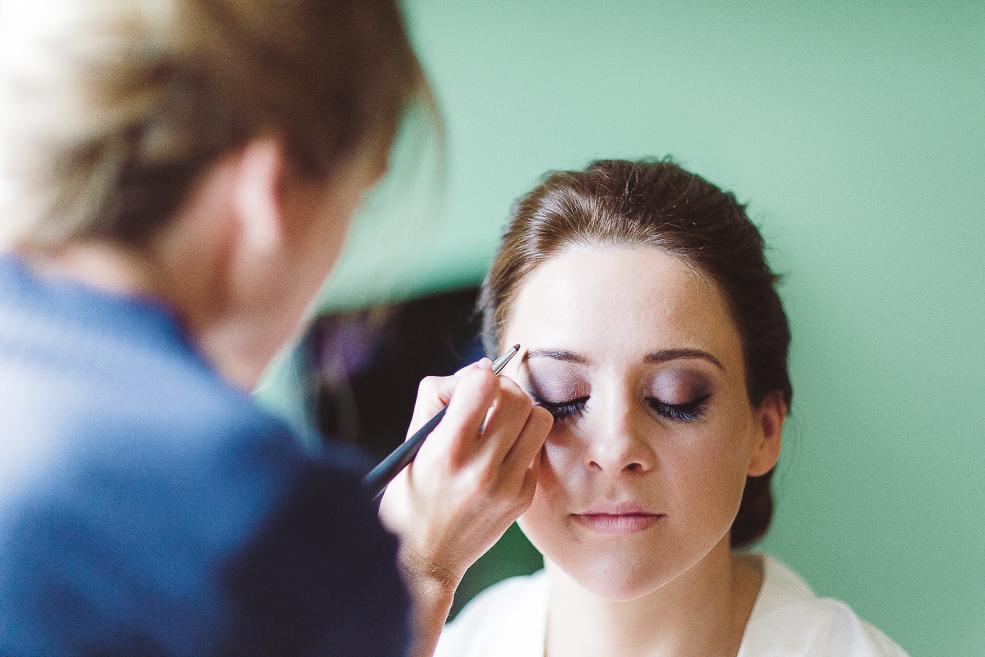 A woman in a blue shirt doing a wedding makeup