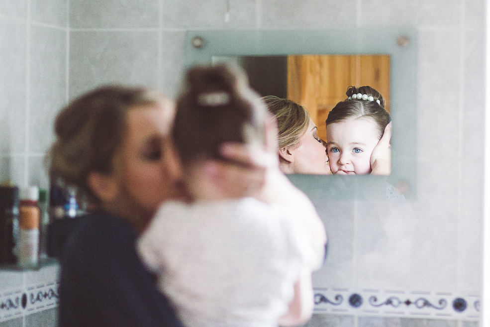 A woman with child standing in front of a mirror