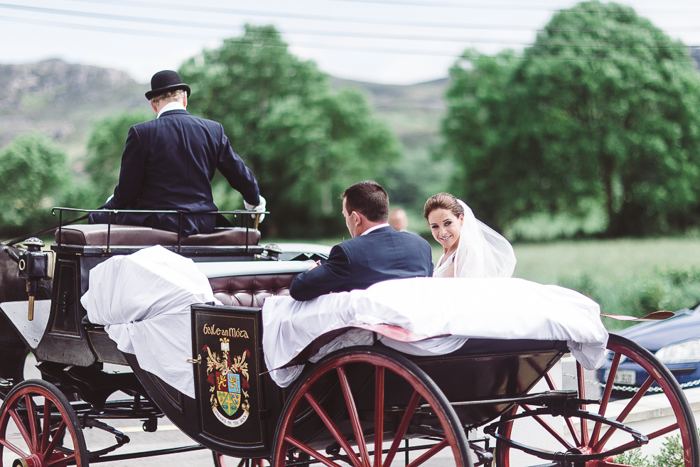 the newlyweds in a horse drawn carriage