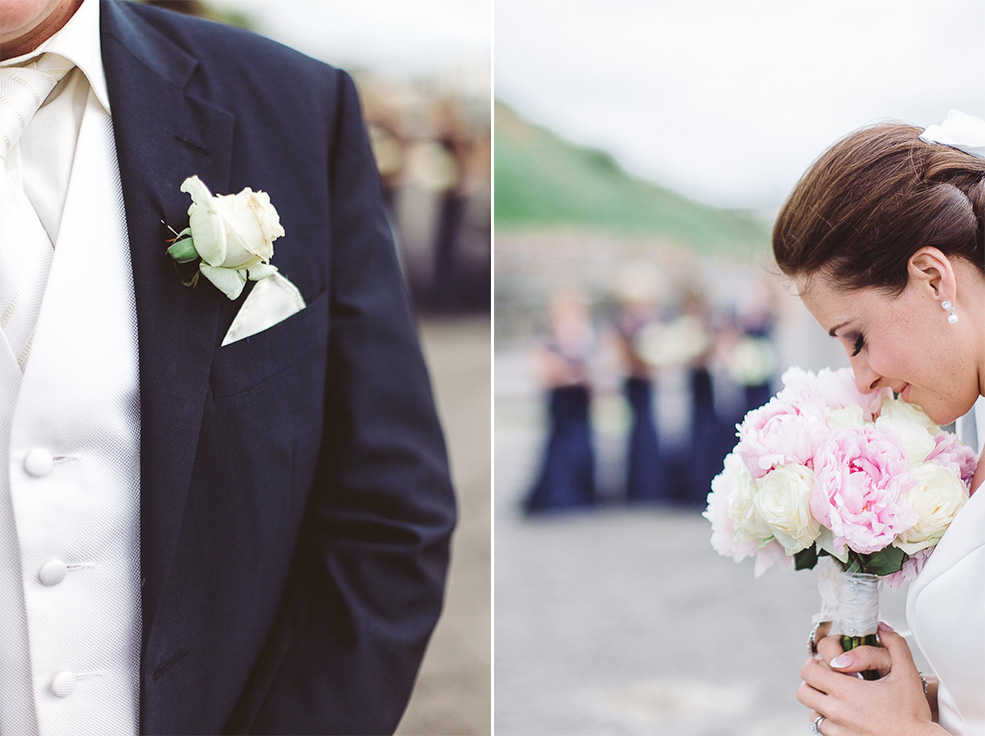 A groom wearing a suit and bride holding the flowers