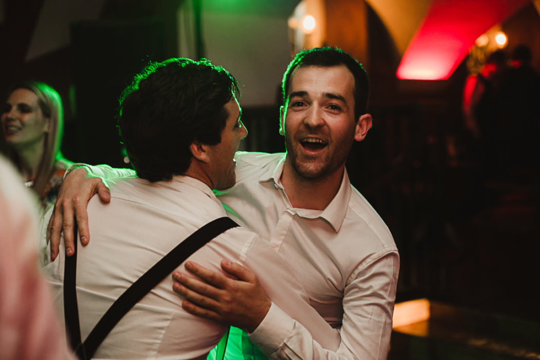 A man looking at the camera dancing and smiling