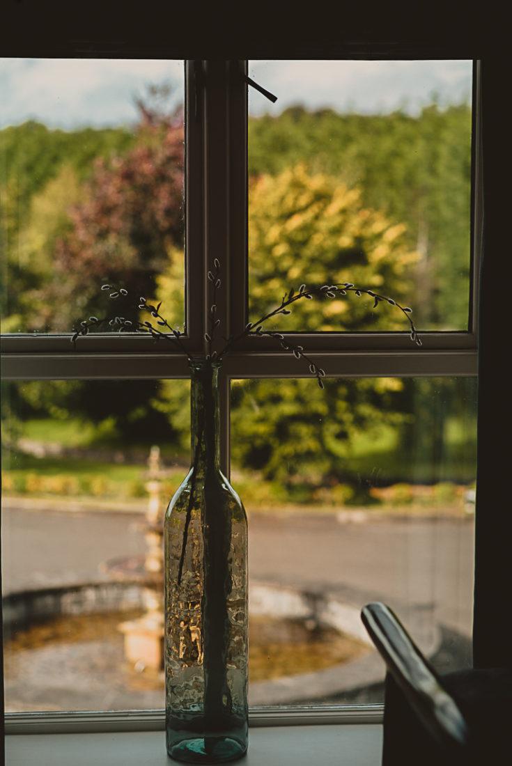 A glass of wine next to a window