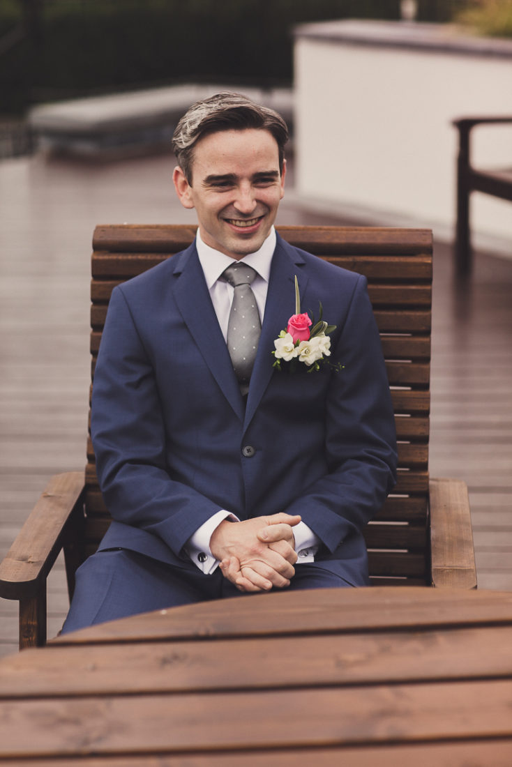 A person wearing a suit and tie sitting on a bench