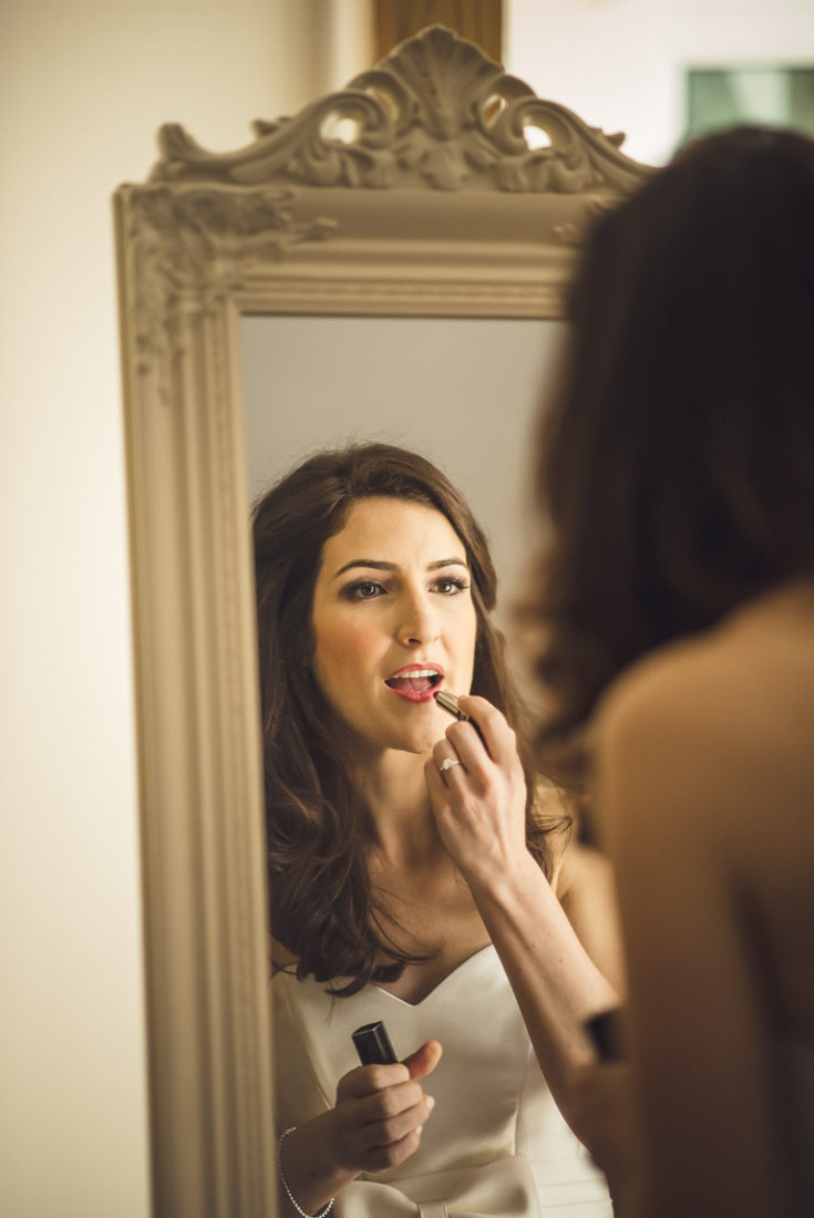 A woman brushing her teeth in front of a mirror posing for the camera
