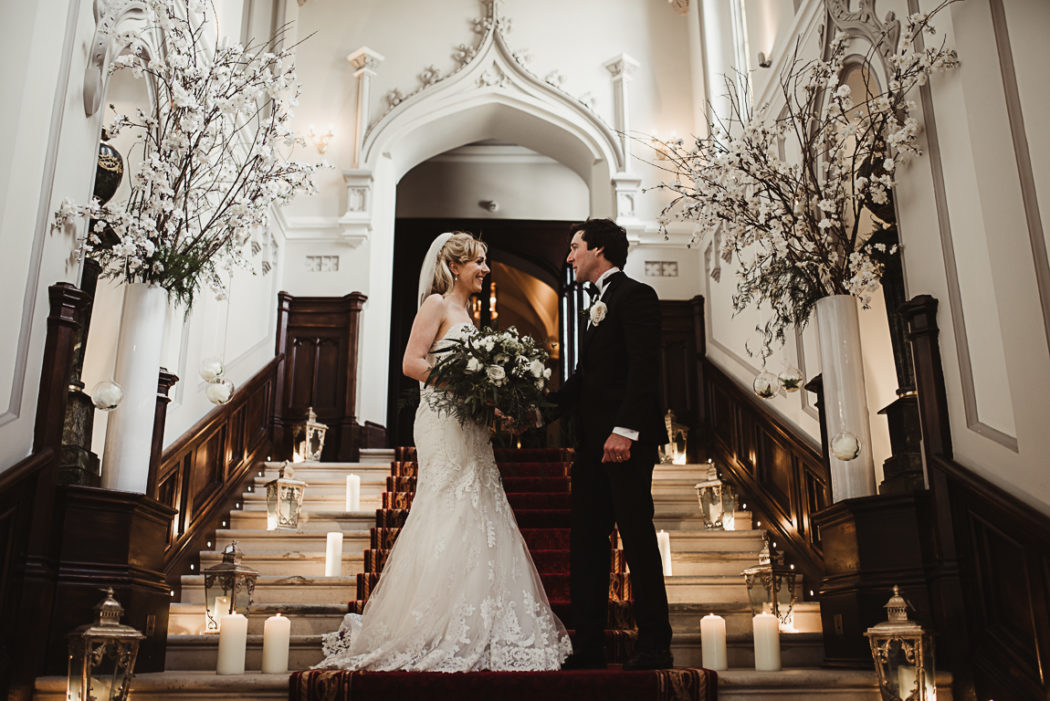 Photograph of the newlyweds on stairs with candles around