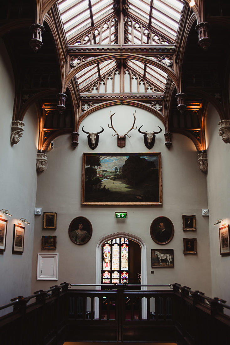 A room with a large painting and trophies