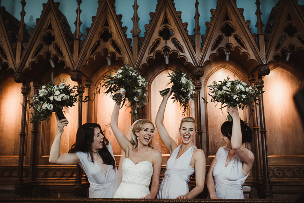 Women in white wedding dresses holding flowers above their heads