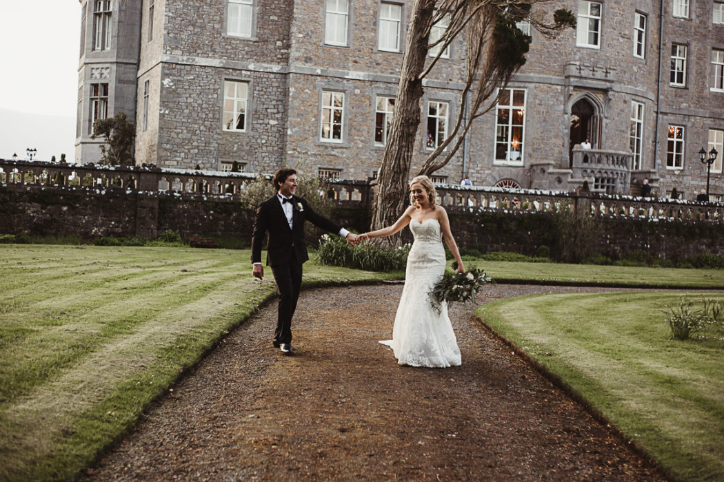 A bride and groom holding hands in front of Markree Castle