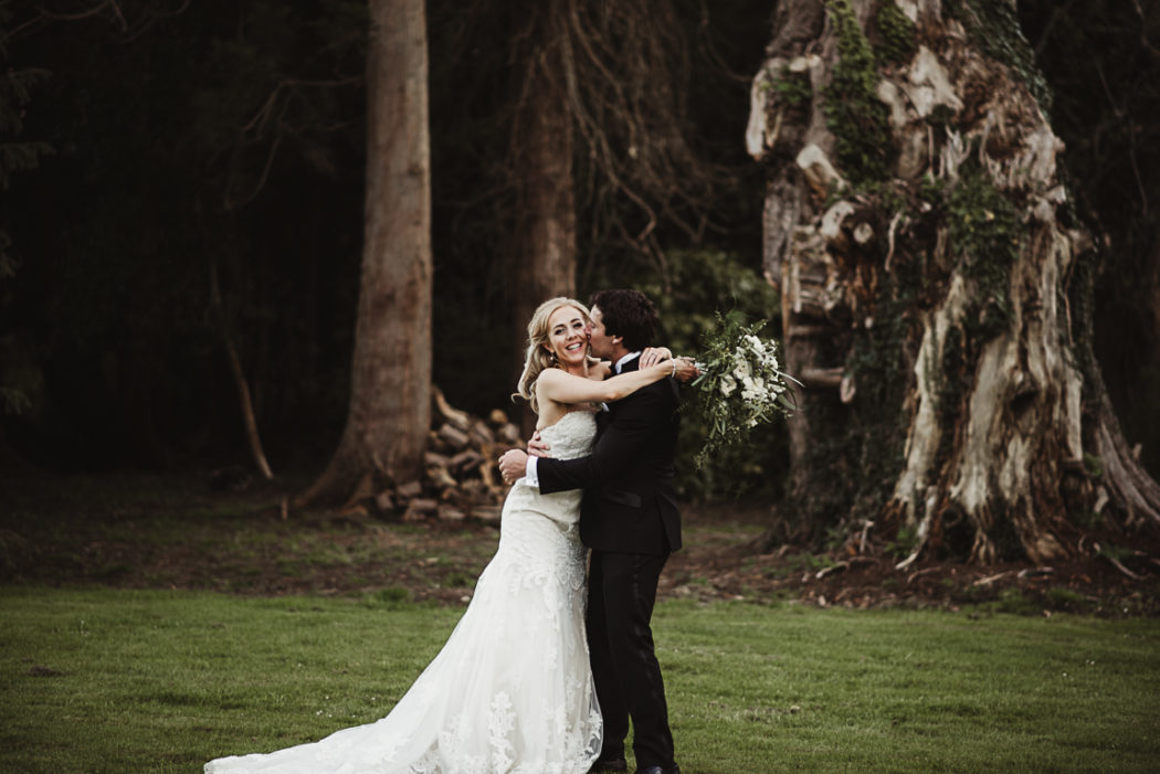 Bride and groom standing next to a forest