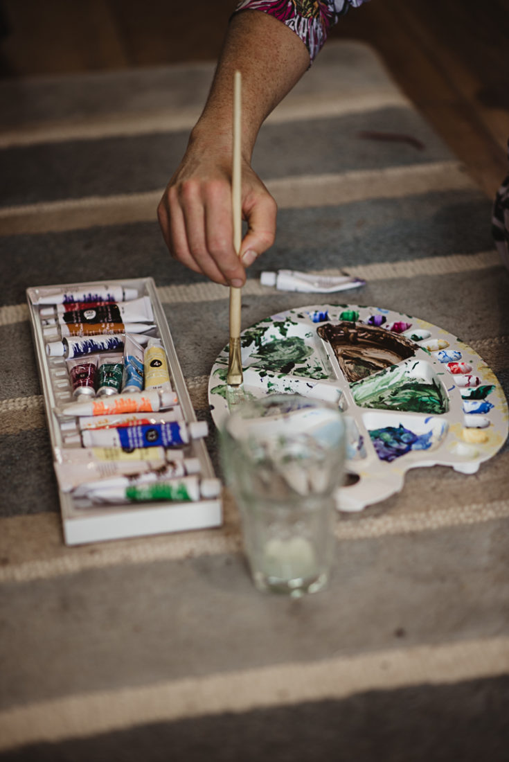 A hand holding a brush and paints