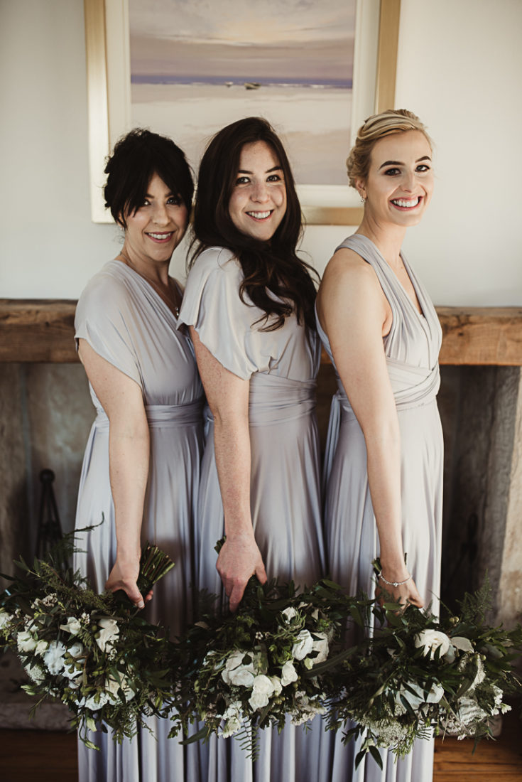 Three women posing for a picture holding flowers