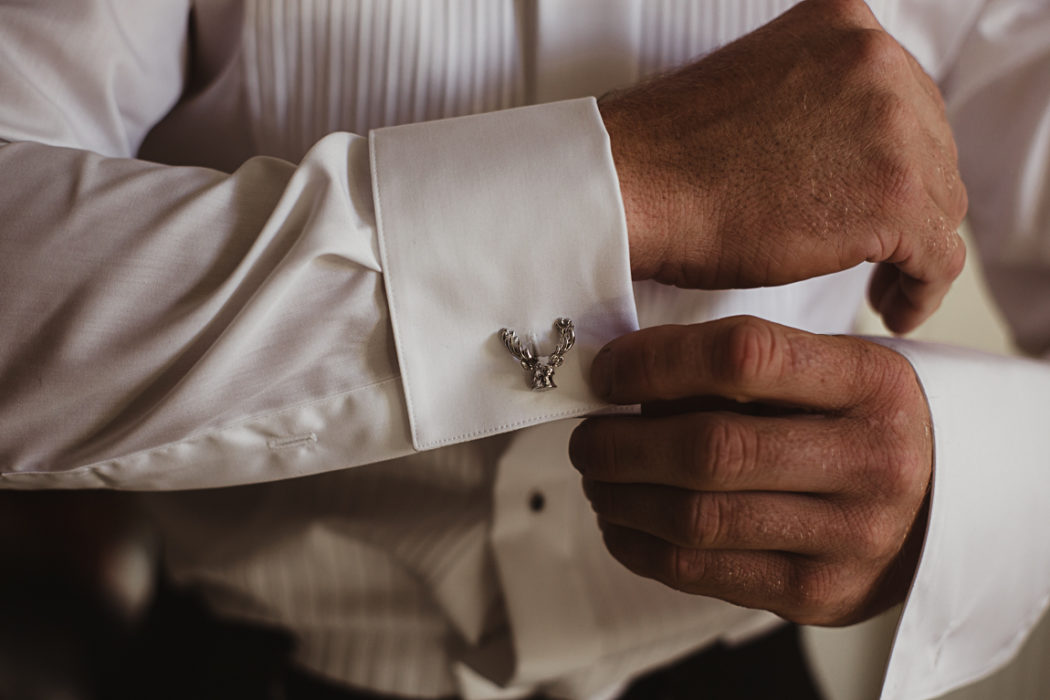 A groom buttons the cuff