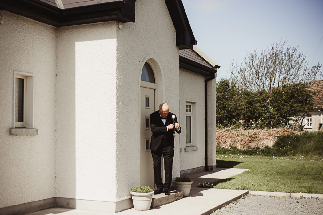 A man standing in front of a house before the wedding ceremony