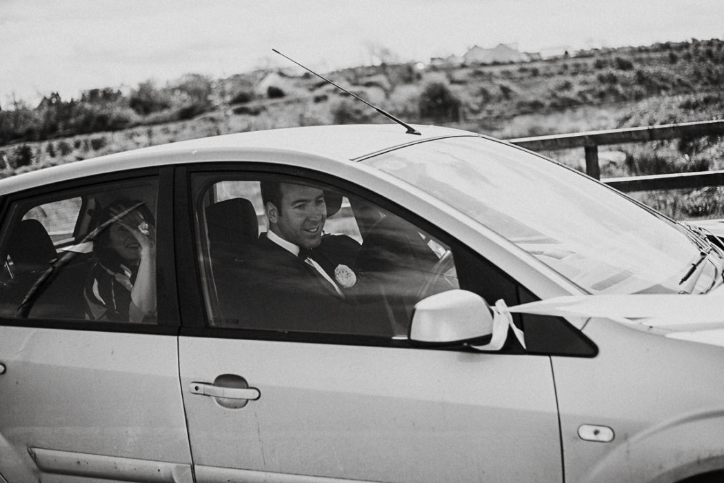Black and white car photography with groom inside