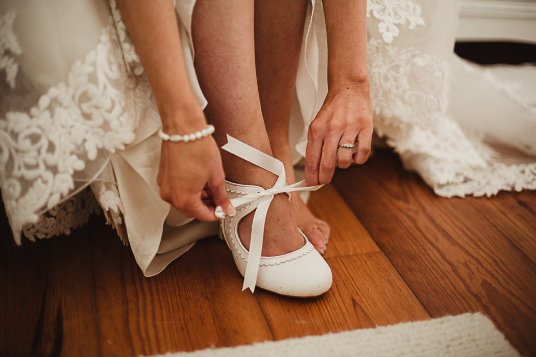 Bride wearing shoes on a wooden floor