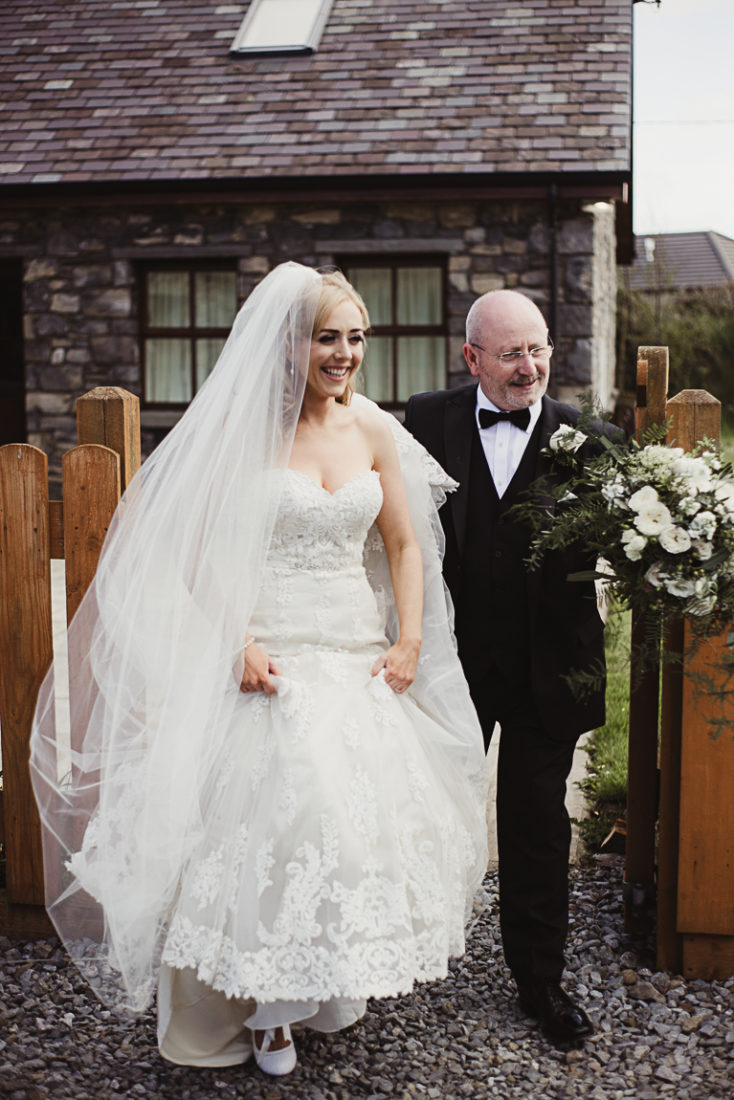 A bride in a wedding dress with her father