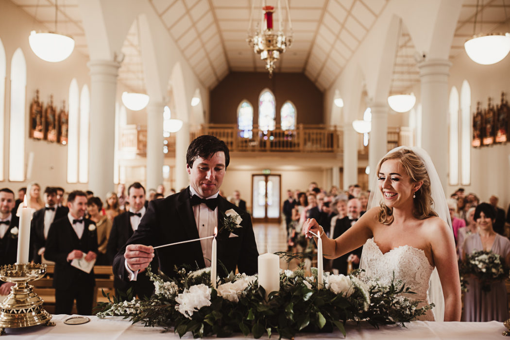 The newlyweds linghting candles in a church