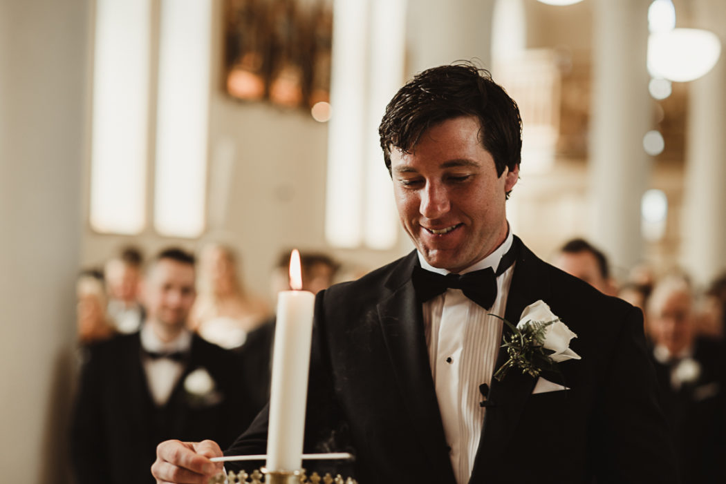 A groom wearing a suit and tie in a church with a candle