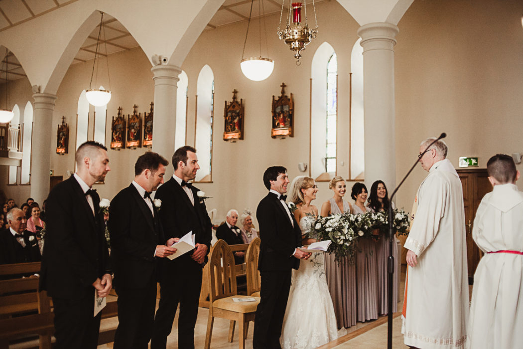 A The newlyweds and group of people standing in church