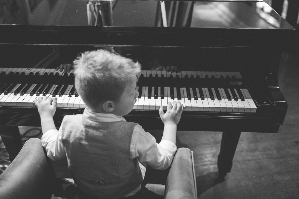 A boy sitting in front of a piano