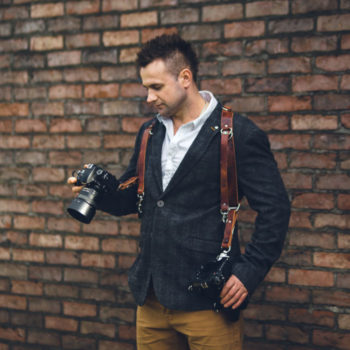 Wojciech Koza - documentary wedding photographer standing in front of the brick wall looking at the camera