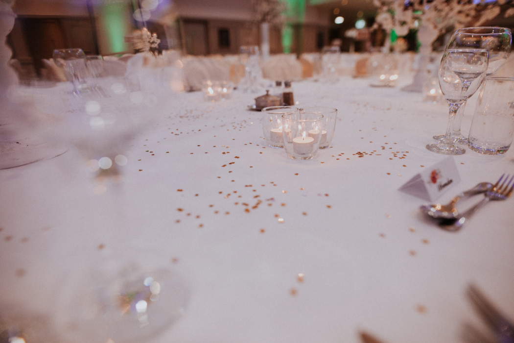 A piece of cake on a table with wine glasses