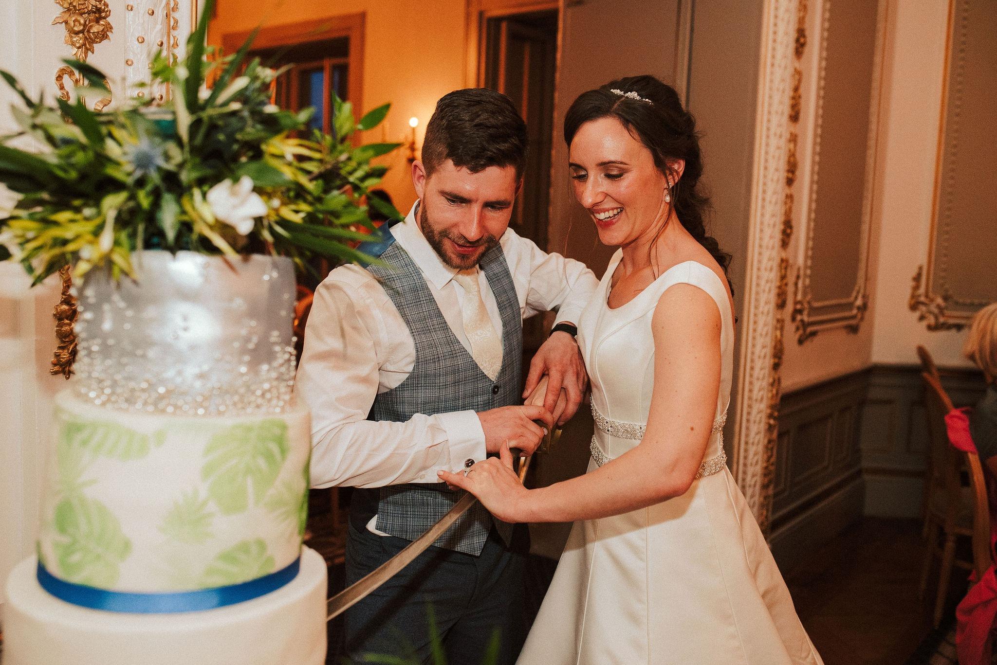 A man and woman cutting a wedding cake