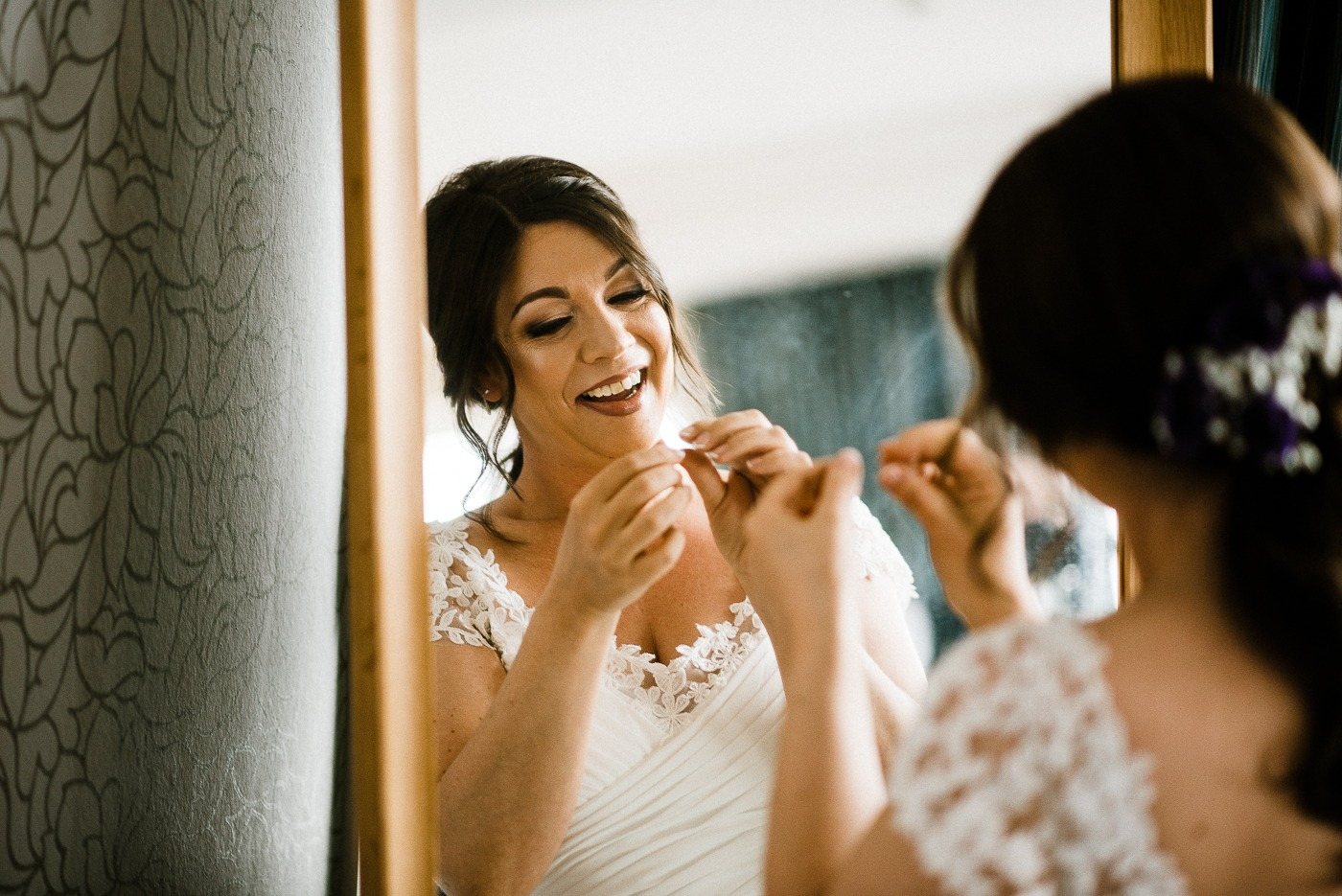 A person brushing the teeth in front of a mirror posing for the camera