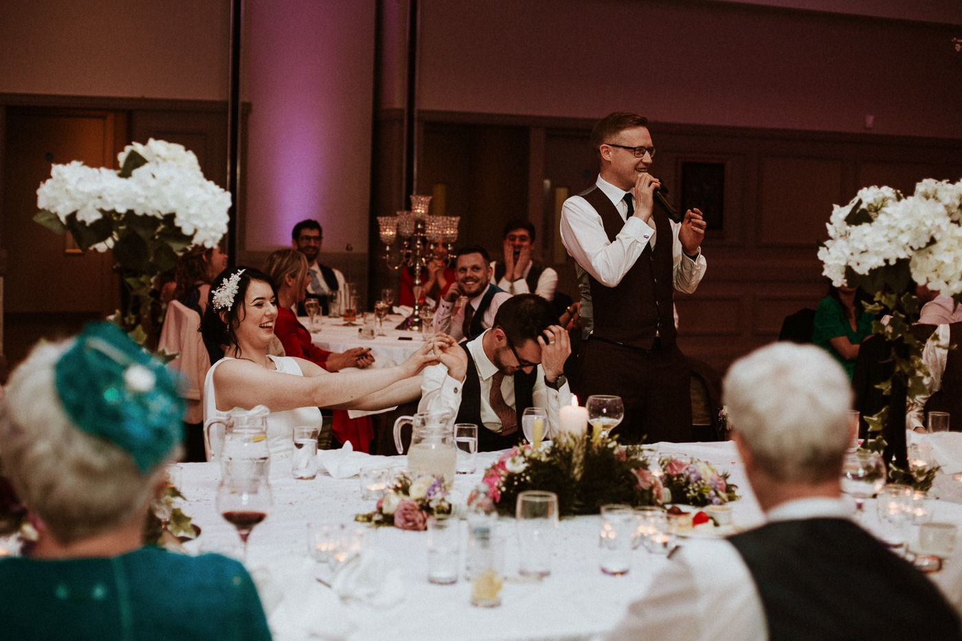 A group of people sitting at a table in front of a wedding cake