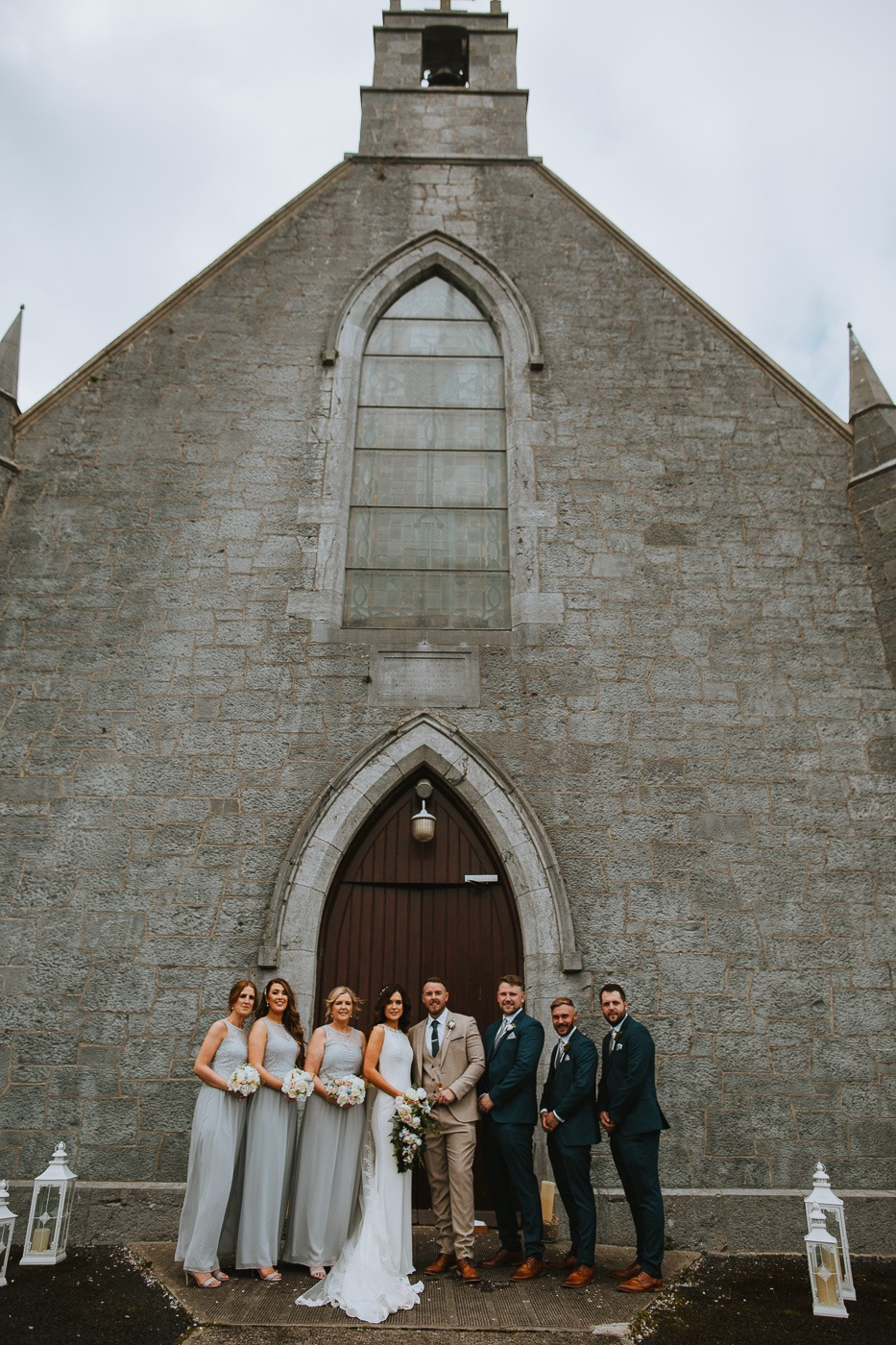 A group of people standing in front of a stone building