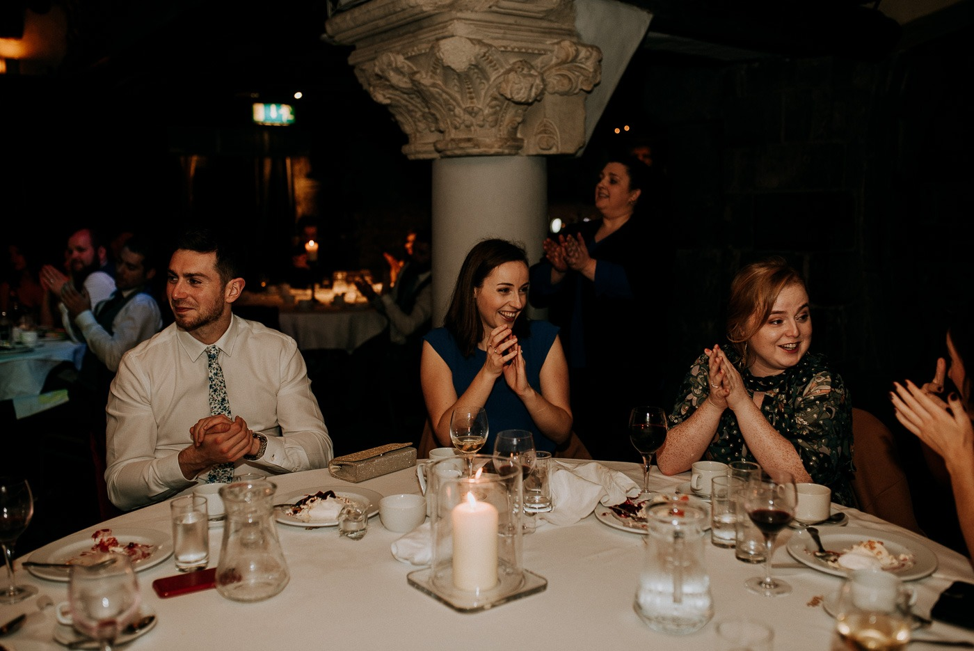 A group of people sitting at a table with wine glasses