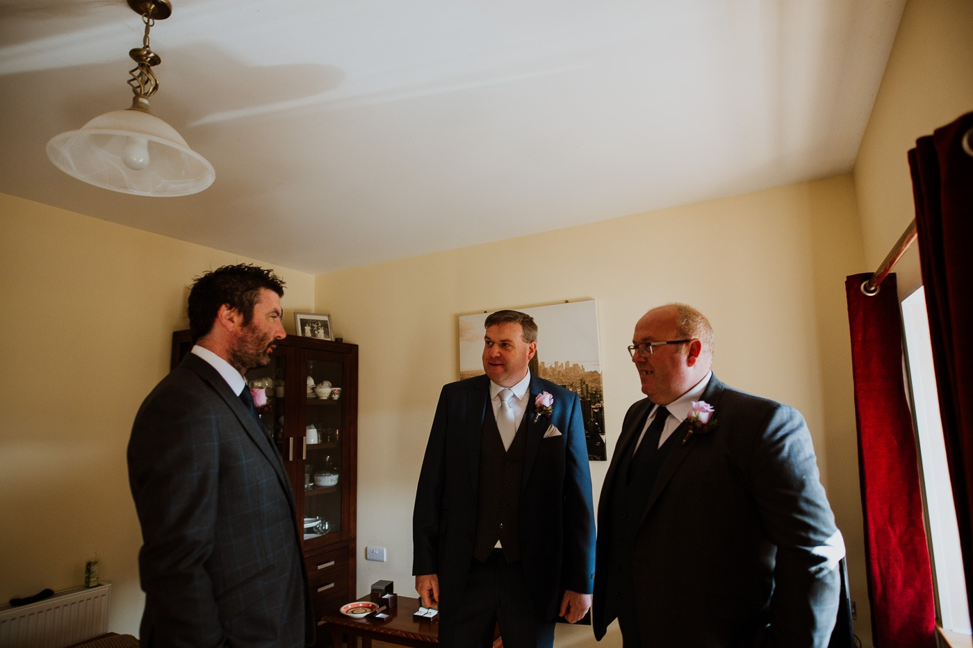 A man wearing a suit and tie standing in a room