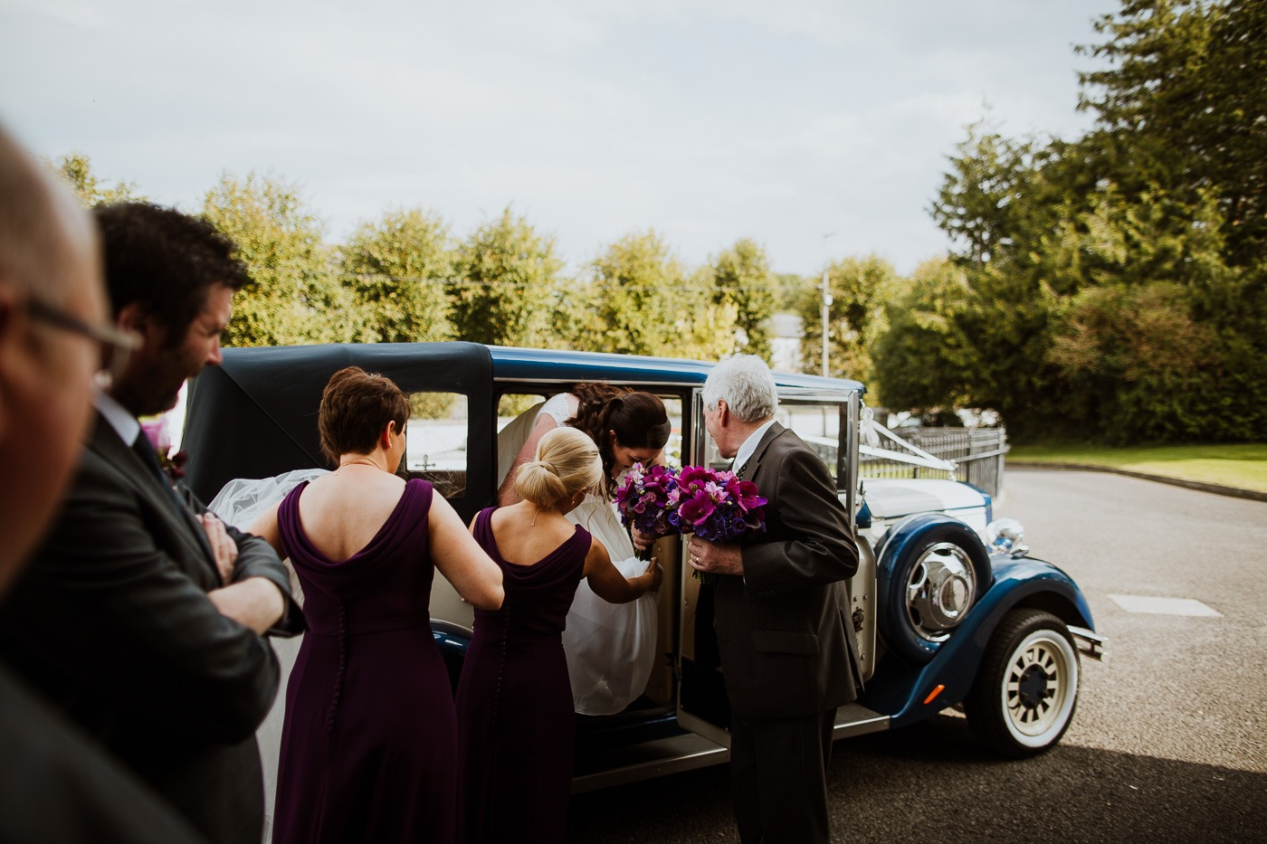 A group of people standing in front of a car