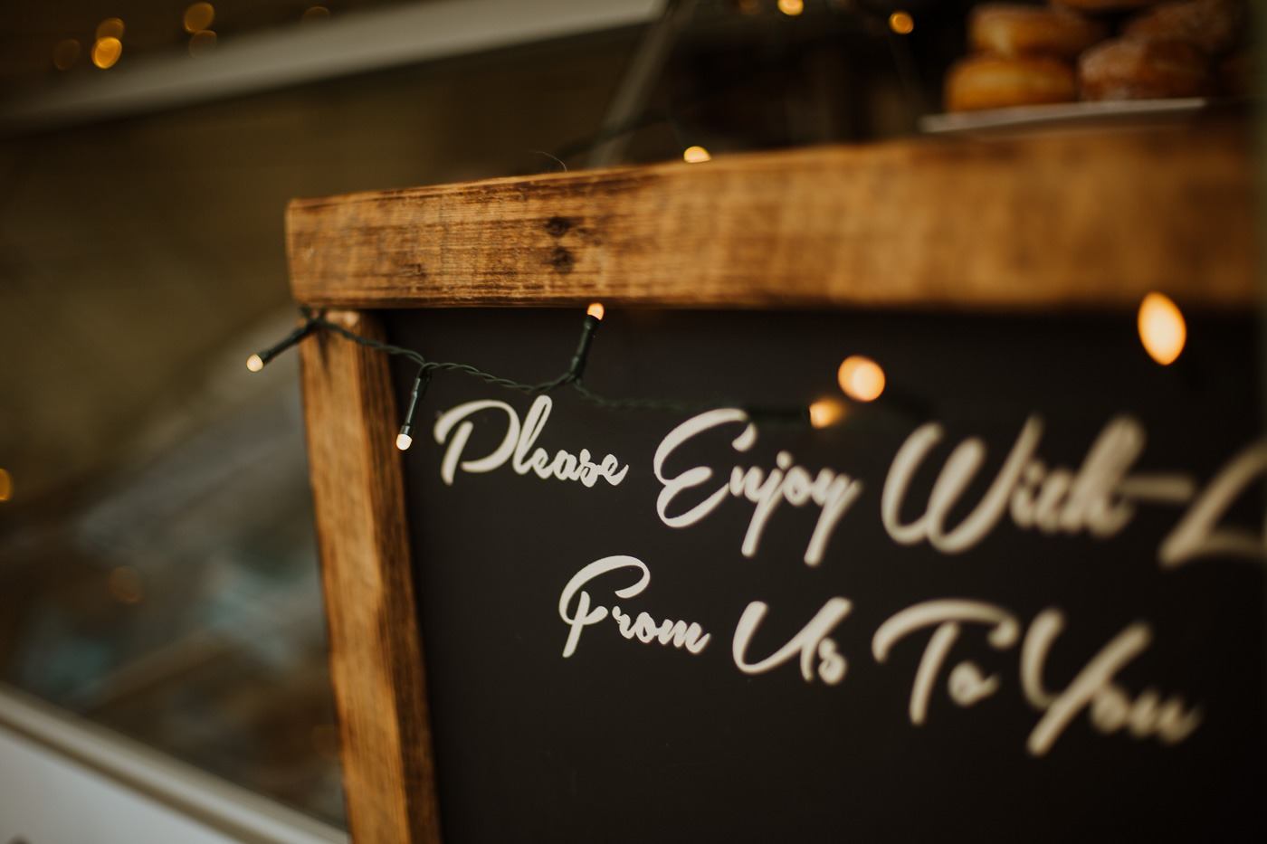 A black sign with white text on a wooden table
