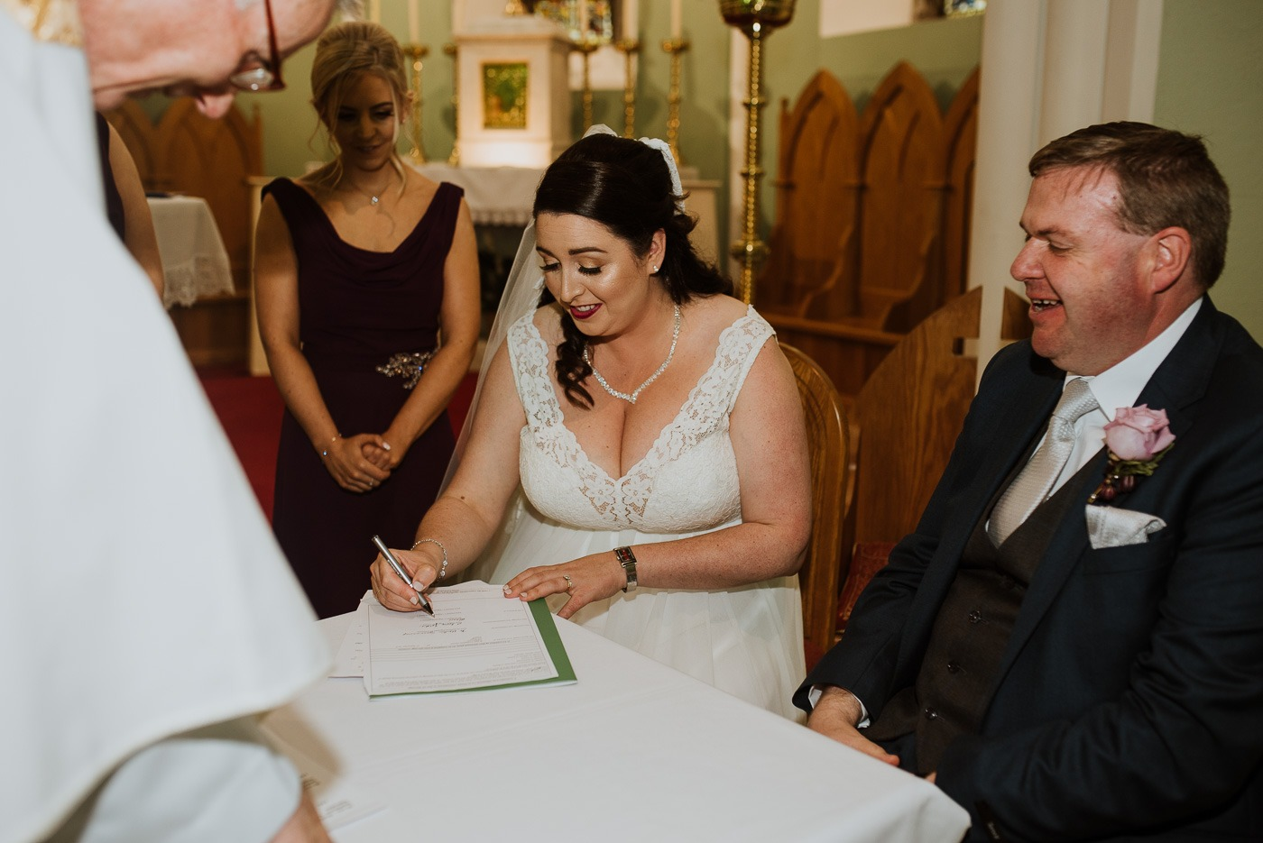 A couple of people that are cutting a wedding cake