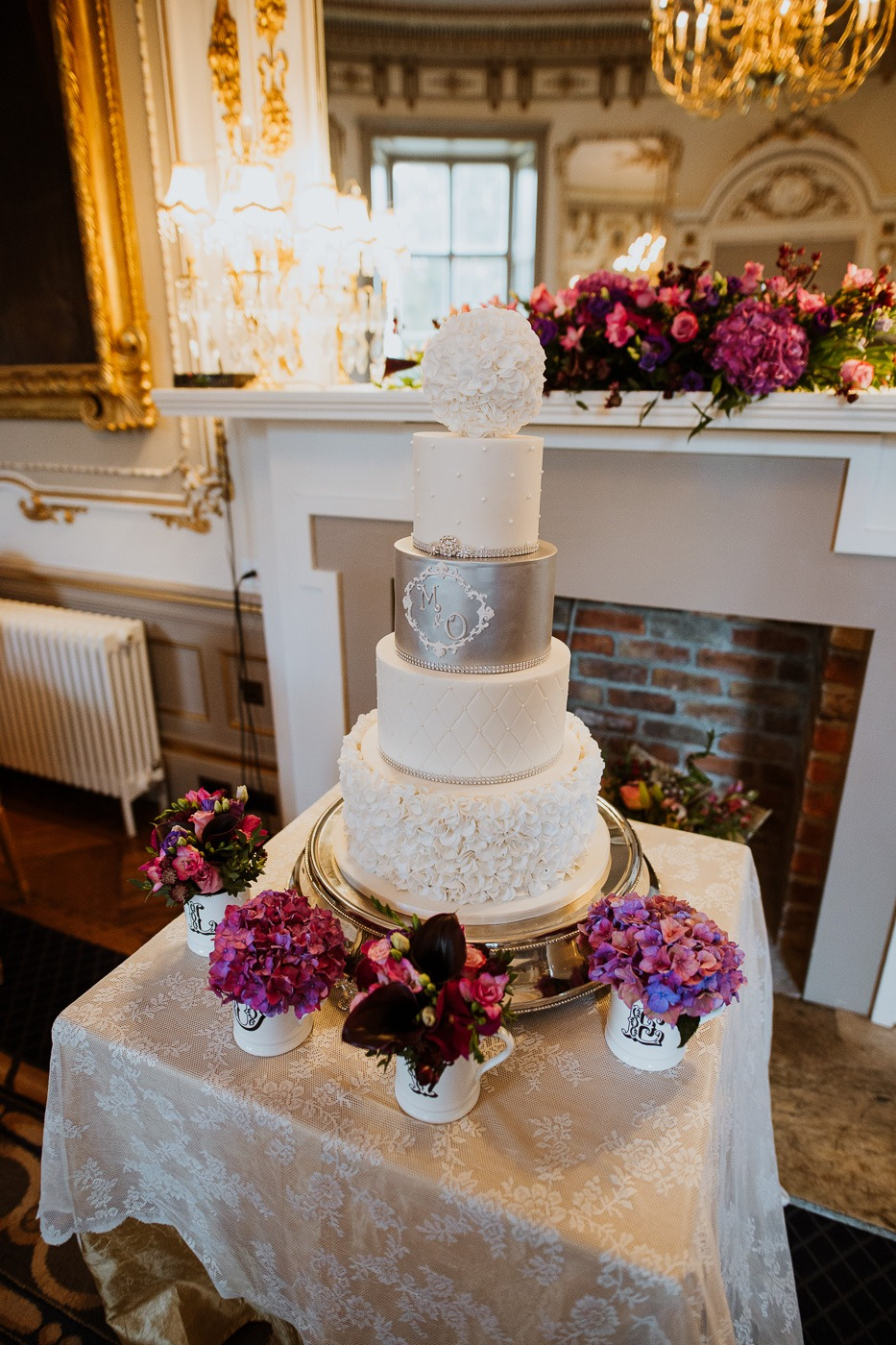 A vase of flowers sitting on top of a wedding cake