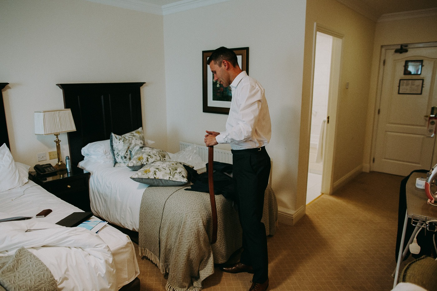 A bedroom with a bed and a man standing in a room