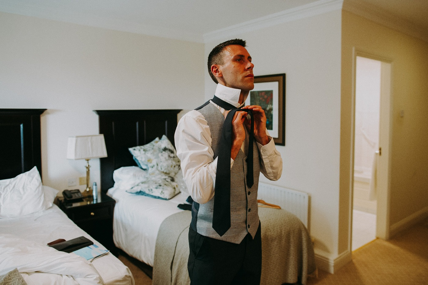 A man wearing a suit and tie standing next to a bed