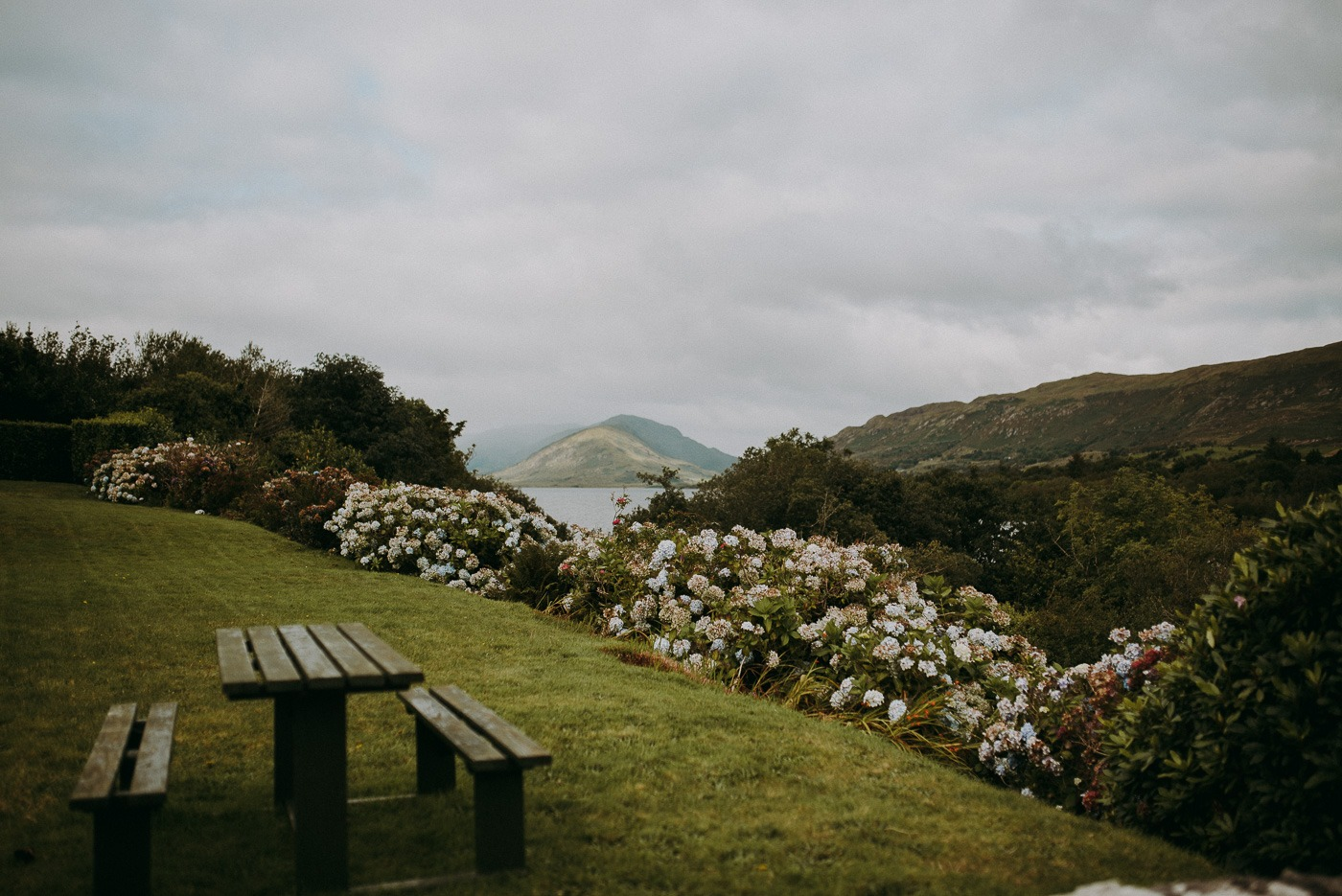 A wooden bench sitting on top of a grass covered field