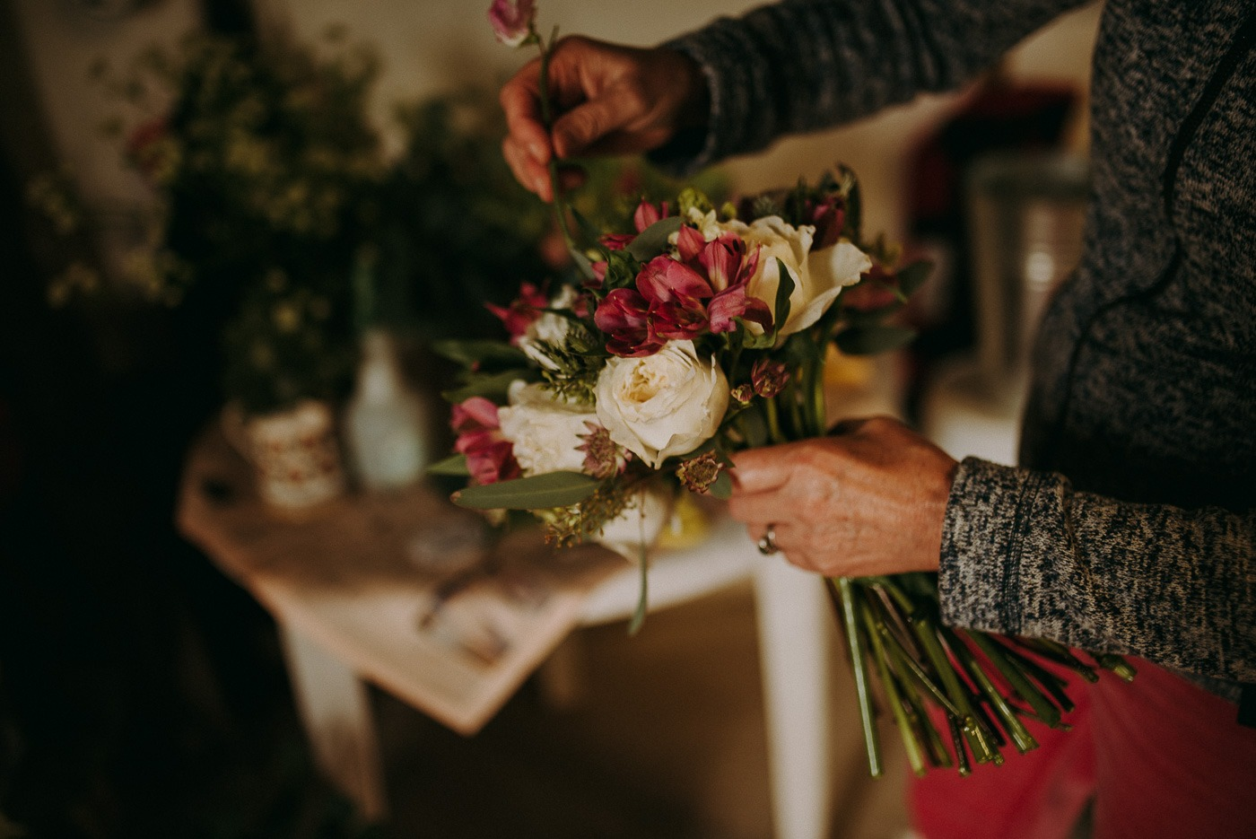 A person holding a vase of flowers on a table
