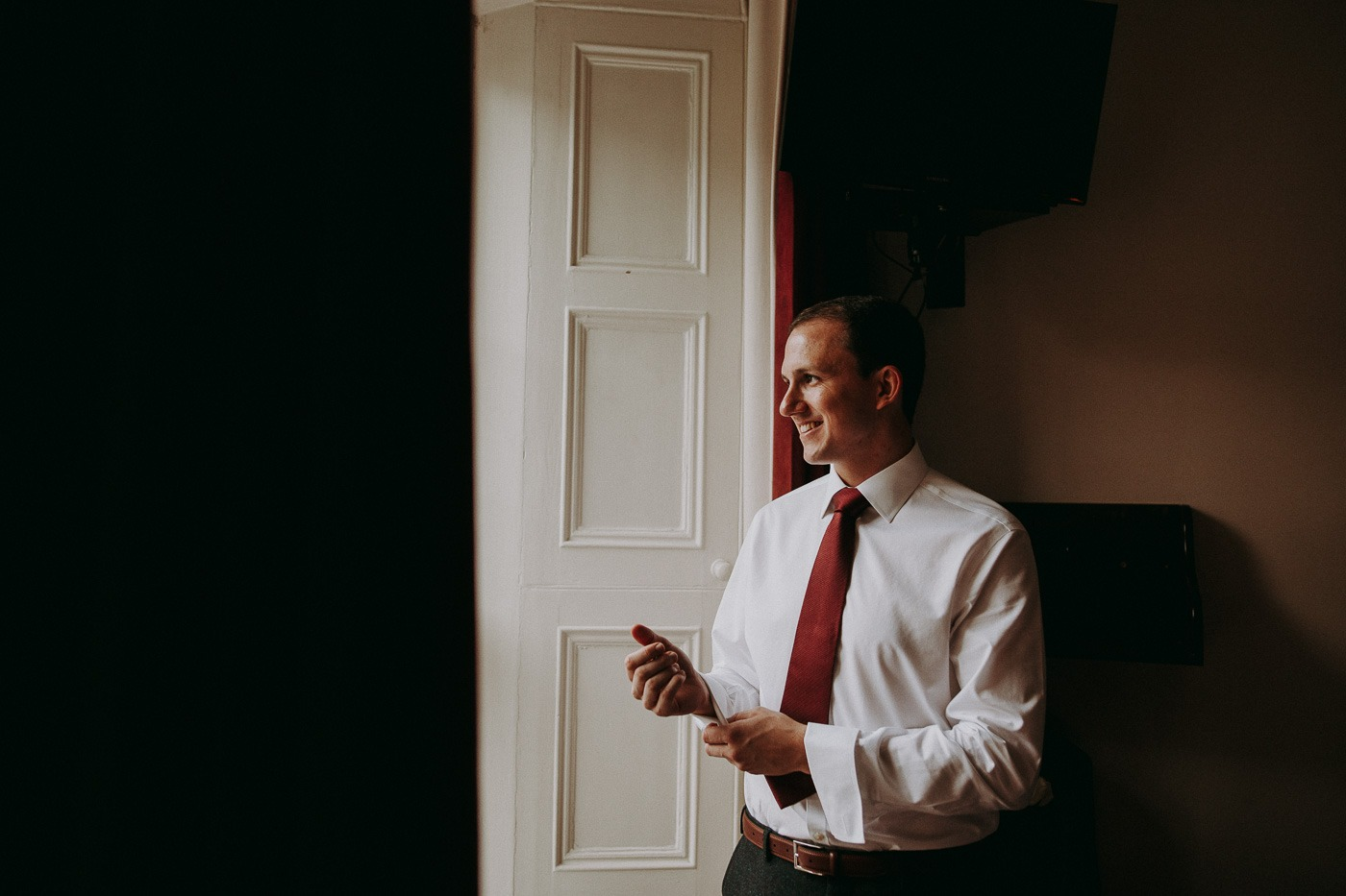 A man wearing a suit and tie standing in front of a door