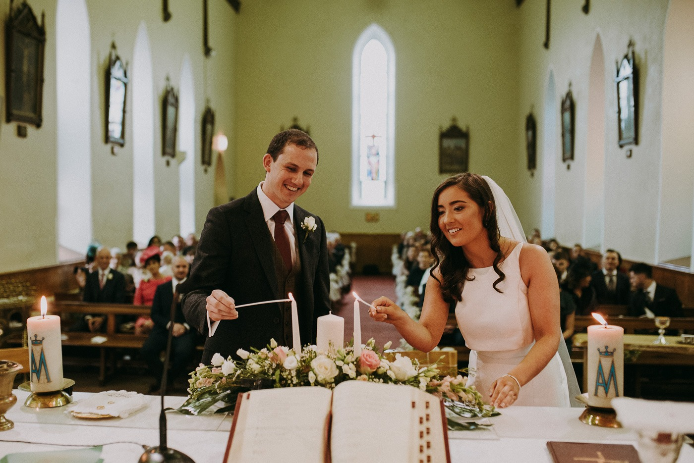 A person cutting a wedding cake
