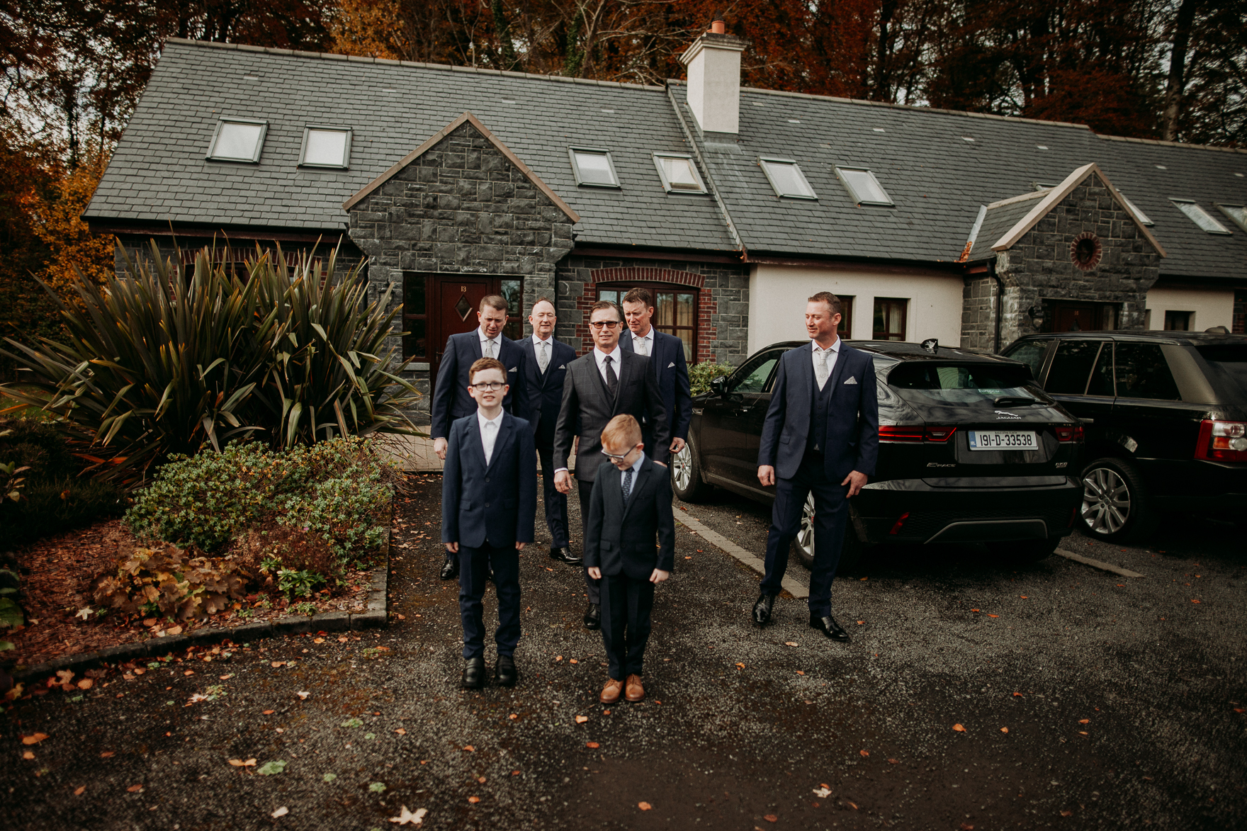 A group of people standing in a parking lot in front of a house