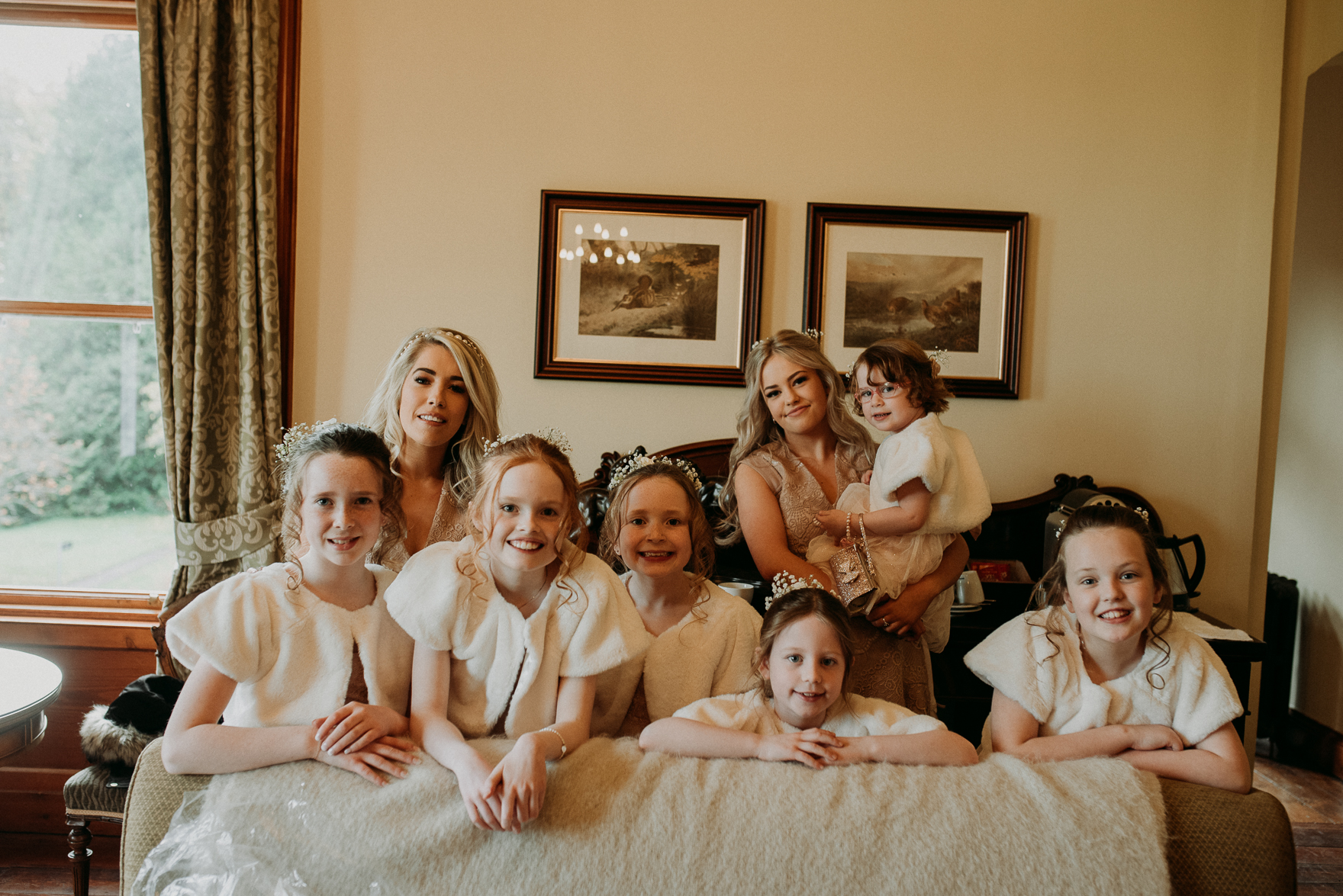 A group of people sitting on a bed posing for the camera