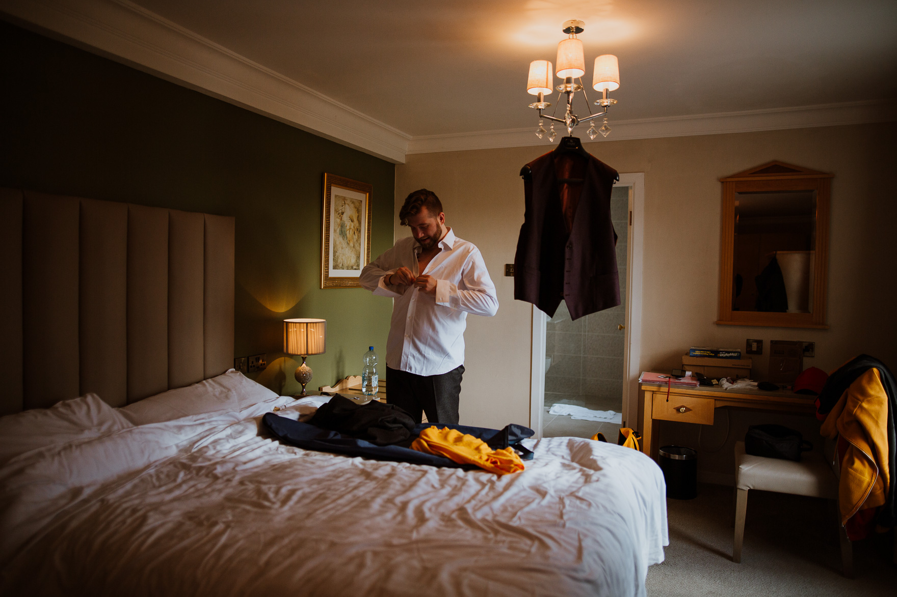 A bedroom with a bed and a person standing in a room