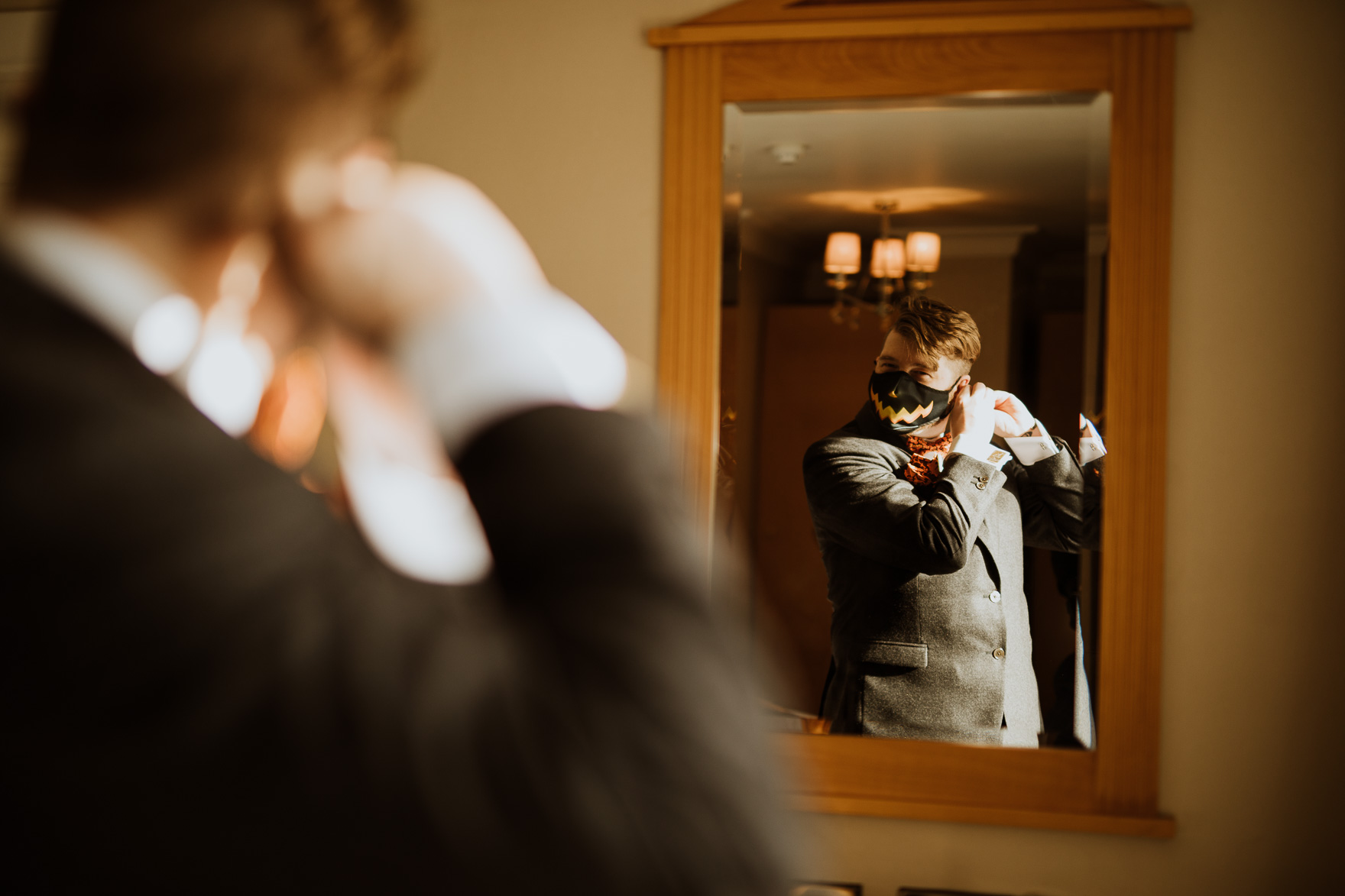 A person holding a cat in front of a mirror