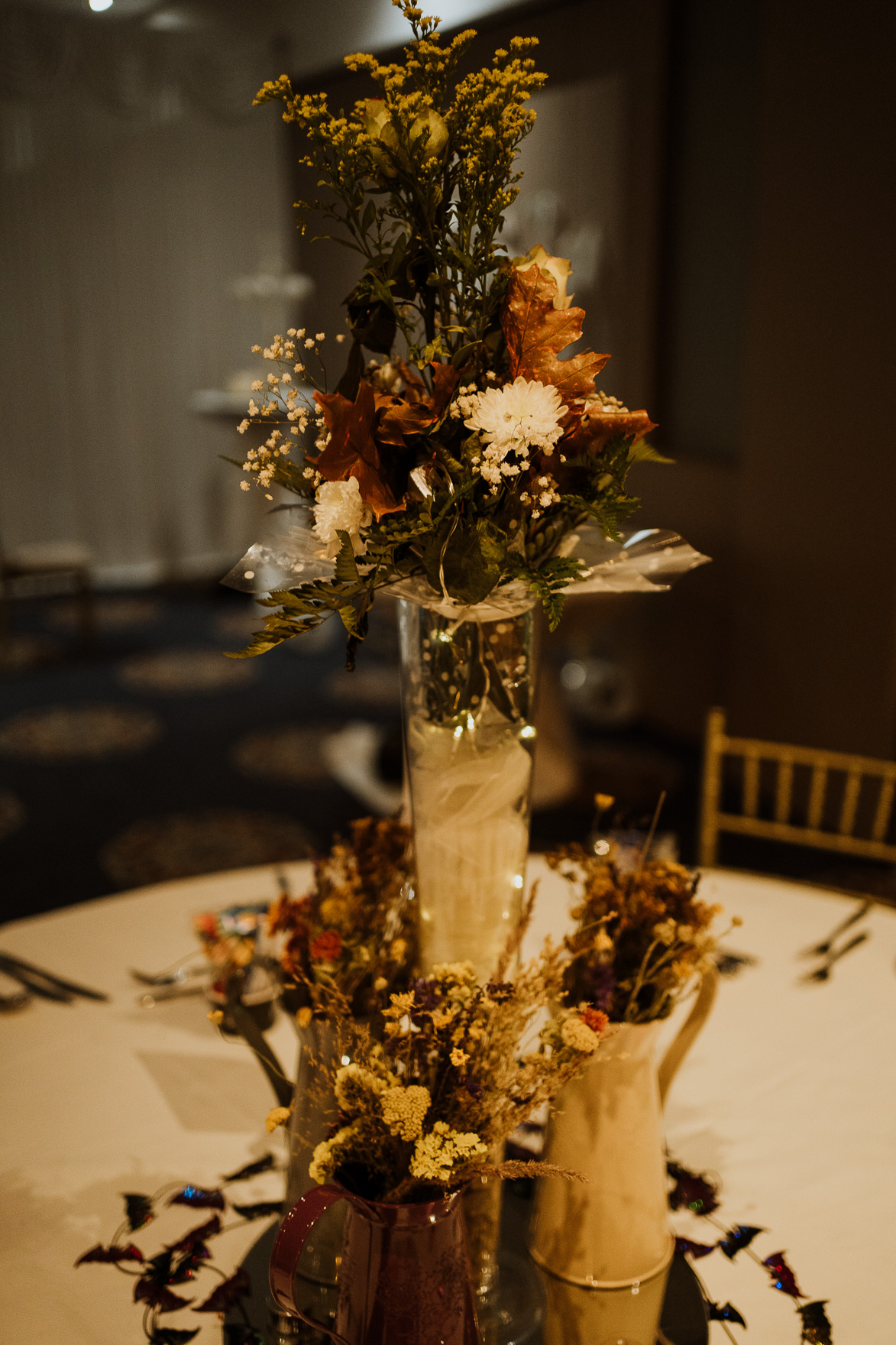 A vase of flowers on a table next to a christmas tree